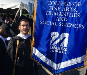 UMass Lowell Alum, Nicholas Gates stands next to the FAHSS banner at Commencement.