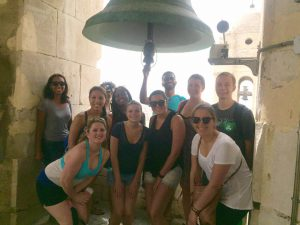 A group photo of UMass Lowell students and faculty at the Vejer Cathedral in Cadiz from a previous Study Abroad trip.
