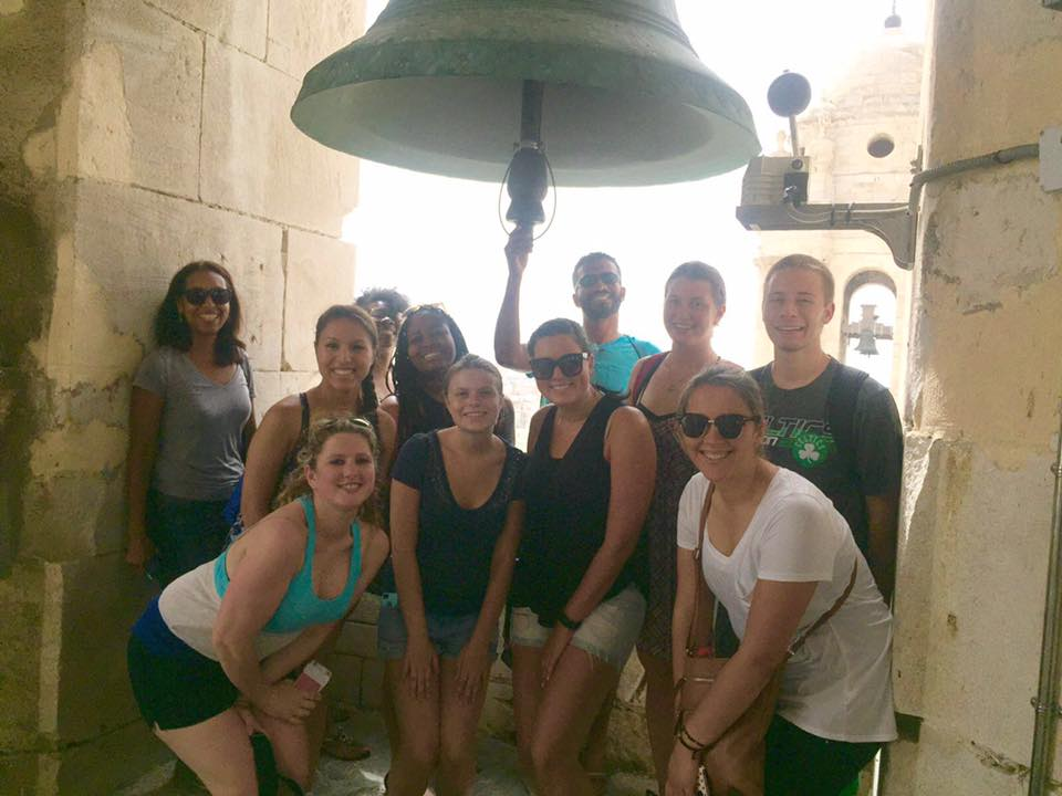 students pose for photo under the bell at the top of Vejer Cathedral in Cadiz, Spain