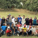 Honors College students pose with Cuban little league baseball players on the field in Finca Vigia, the Cuban home of writer Ernest Hemingway.