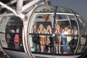 Students peer from window of the London eye attraction
