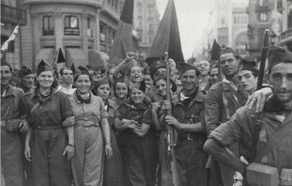 A group of soldiers, male and female, march down a street in Barcelona during the Spanish Civil War.