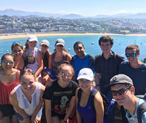 On a sunny day in San Sebastian, Honors College students squint and smile into the camera atop Mount Urgull with the beach La Concha curling behind them.