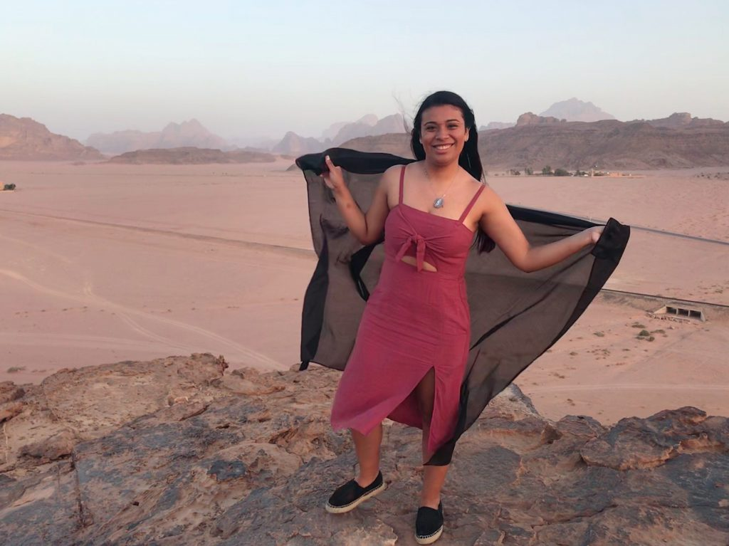 Kelsey Gonzalez-holding a shawl while standing in the desert of Jordan