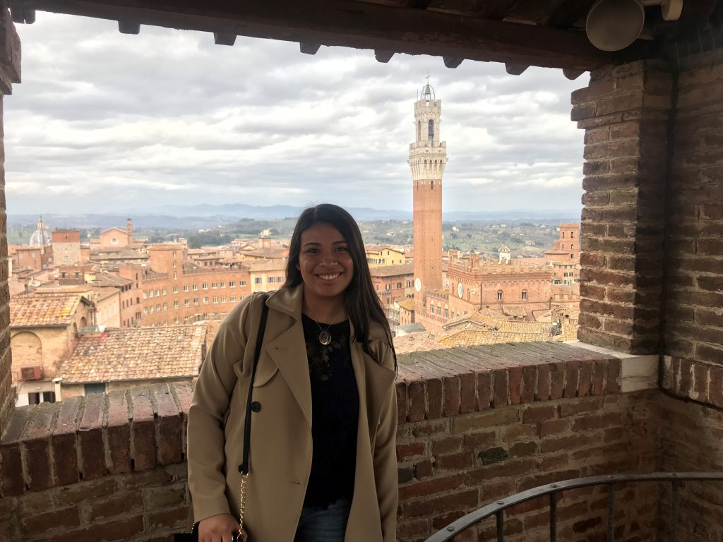 Kelsey Gonzalez-standing atop a bell tower overlooking a city in Italy